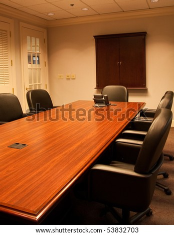 A large empty conference rooms with table and chairs