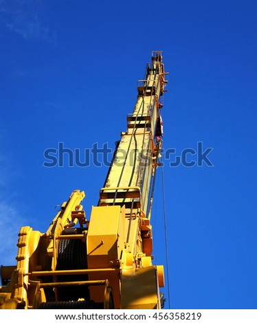 A large extendable crane seen against a blue sky