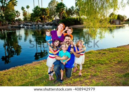 A large family with young parents and young children pose for a family picture by a lake. - stock photo