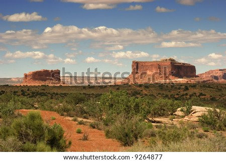 A large field in beautiful Moab Utah showing massive red rock coming up from the earth.