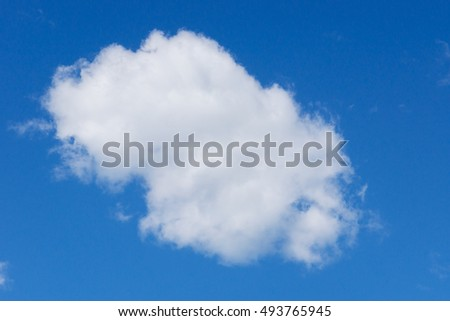 A large, fluffy, oval shaped cumulus cloud set against a deep blue sky