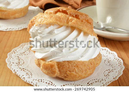A large golden cream puff on a doily with a cup of coffee - stock photo
