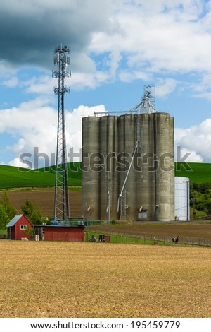 A large grain silo storage building with a cell phone tower