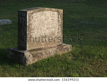 A large gravestone in a graveyard, shot in the golden light of dusk.  - stock photo
