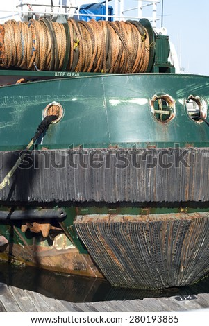 A large, green freighter in port with layered rubber bumpers to protect the hull from damage. - stock photo