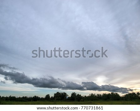 A large, grey cloud hangs over a rice field in eastern Thailand