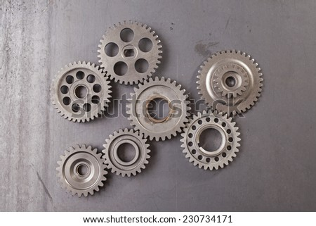 A large group of interlocking metal gears on a grungy steel background - stock photo