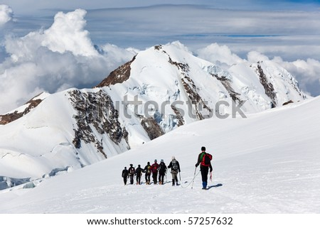 A large group of mountaneers walking on a glacier in a sunny day: in background the snowed peaks of Lyskamm (4550 mt) , Monte Rosa range, West Alps, Switzerland, Europe. - stock photo