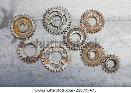 A large group of rusty gears linked together on a steel background. - stock photo