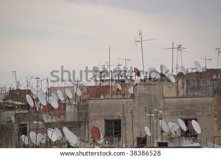A large group of satellite dishes on the rooftop - stock photo