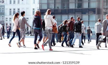A large group of young men and women walking. The urban landscape.