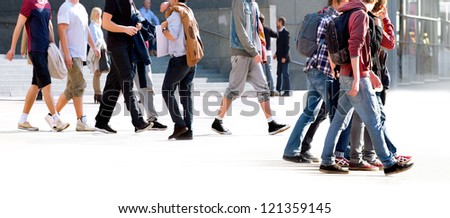 A large group of young people walking. The urban landscape.