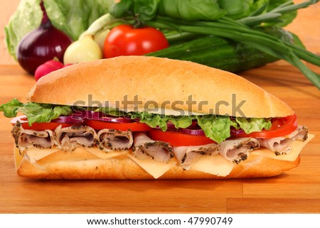 A large ham and tomato sandwich, on a wooden board - stock photo