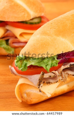 A large ham and tomato sandwiches, on a wooden board - stock photo