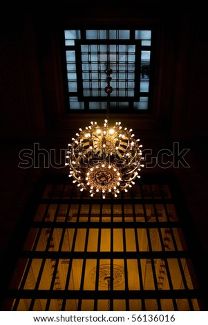 A large hanging chandelier inside the New York Grand Central Terminal train station. - stock photo