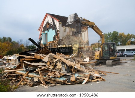 A large house being demolished by a backhoe.  Rubble in foreground. - stock photo