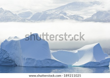 A large iceberg floats just off shore in Baffin Bay, Greenland. - stock photo