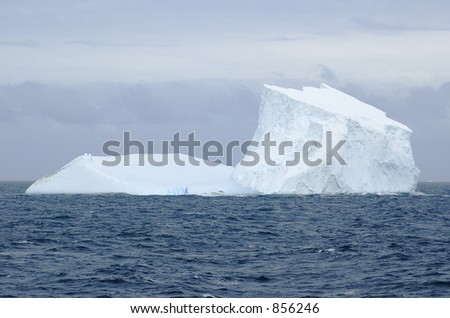 A large iceberg in the South Atlantic. To the left are a large number of penguins; above the iceberg in the center are a number of birds in flight. - stock photo