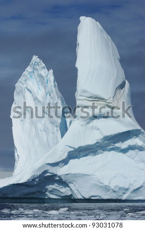 A large iceberg with two peaks floating in the ocean. - stock photo