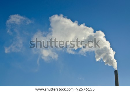 A large industrial smokestack sends smoke up into a clear blue sky. - stock photo