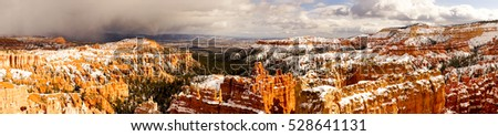 A large long panoramic of Bryce Canyon with a snow storm moving in
