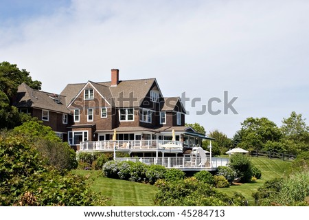 A large luxury home with a deck pool and nicely landscaped grounds. - stock photo