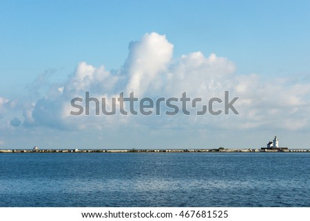 A large mass of cumulus clouds form over Lake Erie as seen from inside the break wall at the Port of Cleveland, Ohio.  On the right is a lighthouse style navigation beacon at the harbor entrance