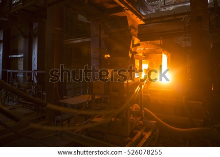 A large melting furnace.Glass recycling. Bottle manufacturing industrial factory. Molten glass