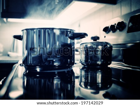 A large metal pot emitting steam on a stove top with another smaller pot. - stock photo