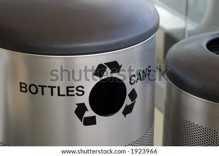 A large metal recycling container in a public area with a hole for bottles and cans - stock photo