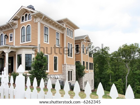 A large middle-class home with a white picket fence. - stock photo