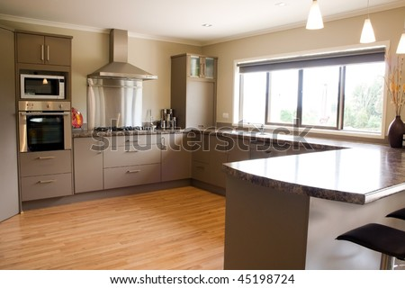 A large modern kitchen with stainless steel accessories and wooden floor - stock photo