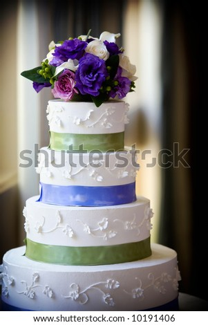A large multi level wedding cake with purple flower topper