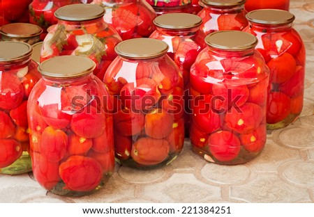 A large number of glass jars with red ripe tinned tomatoes. Are corked with metal covers. - stock photo