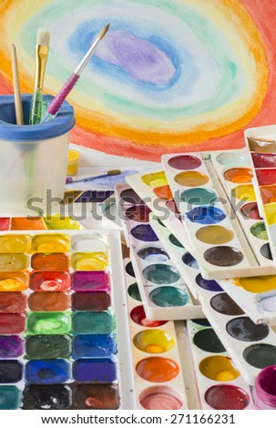 a large number of watercolor  paints and brushes on the table