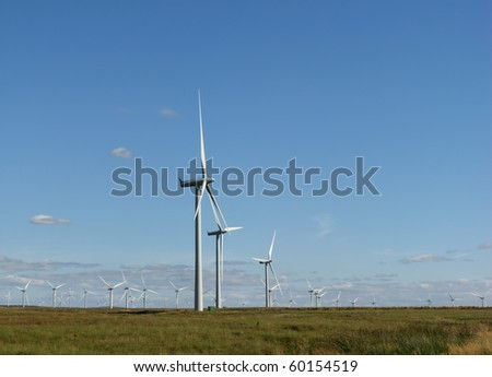 A large number of wind turbines on a wind farm with blue sky - stock photo