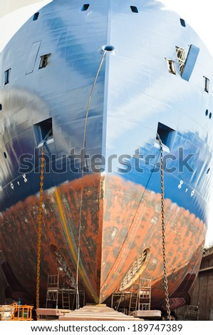 A large offshore vessel with an X-bow type design. Long and rusty anchor chain deployed - stock photo