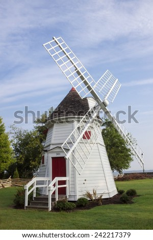 A large old antique vintage white windmill in a grass field on a summer day.