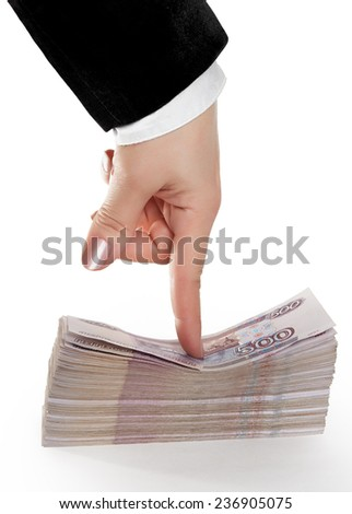 A large pack of Russian banknotes, pinned to the table with the index finger of female hands. - stock photo