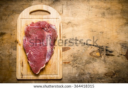 A large piece of raw fresh meat on cutting Board. On a wooden table. Free space for text . Top view - stock photo