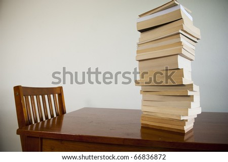 A large pile of books on a table with an empty chair