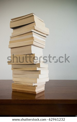 A large pile of books sits on a timber desktop with blank space behind