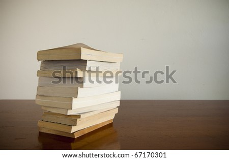 A large pile of books sits on a timber desktop with blank space behind - stock photo