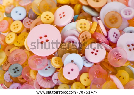 A large pile of pastel buttons. - stock photo