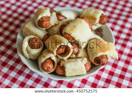 A large plate with a homemade mini hot dogs (hot dogs in pastry) for a large family to the Day of Hot Dog. - stock photo