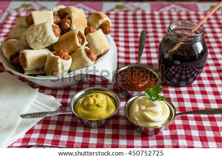 A large plate with a mini hot dogs homemade (sausage dough) with ketchup, mustard, mayonnaise and cola in a glass jar on a plaid background - stock photo