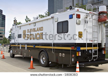 A large police vehicle parked directly outside city hall during a peace rally and air show - Labor Day; Cleveland, Ohio 2006 - stock photo