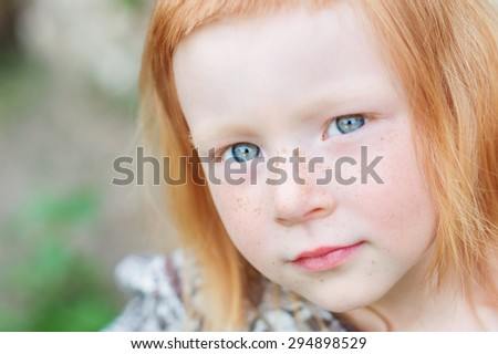a large portrait of a beautiful and delicate red-haired girl with piercing blue eyes - stock photo