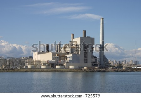 A large power plant churns out electricity to a hungry city (visible in the background). - stock photo