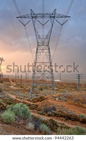 A large power transmission tower and power lines running through the Antelope Valley. - stock photo